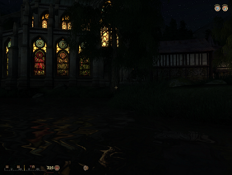 Small screenshot of the PC game, Oblivion, depicting a church with lit stained glass windows reflecting in the water at night.